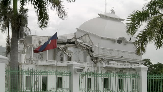 vidéos et rushes de ms detail of collapse roof of national palace with haiti flag flying / port-au-prince, haiti - tremblement de terre