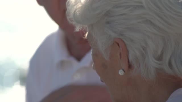 vídeos y material grabado en eventos de stock de detail of couple seniors faces with focus on her and after on him, on terrace by the sea - cabello canoso