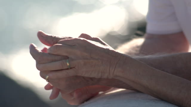 Detail of couple seniors hands with wedding rings on terrace by the sea