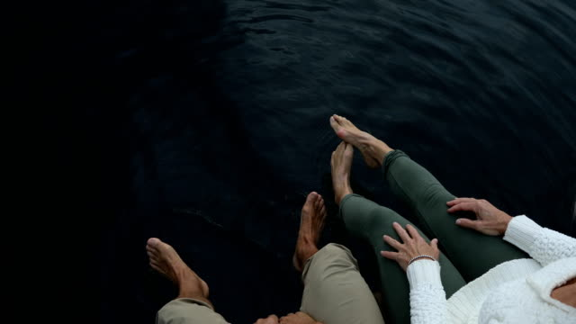 detail of couples feet in dark lake water at sunrise - mature couple stock videos & royalty-free footage