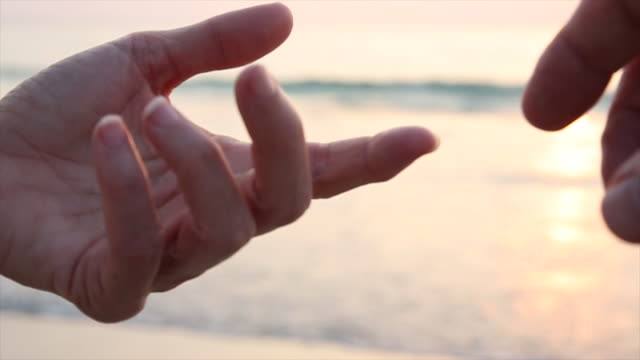 detail of couples' fingers touching above calm sea - sensory perception stock videos and b-roll footage