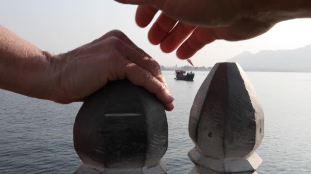 vídeos de stock e filmes b-roll de detail of couple's hand on post above lake and floating palace - casal de meia idade