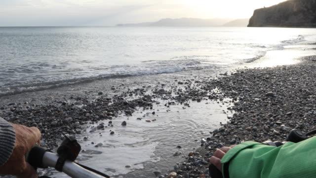vídeos de stock e filmes b-roll de detail of couple's hands on bike handlebars near sea at sunrise - guiador