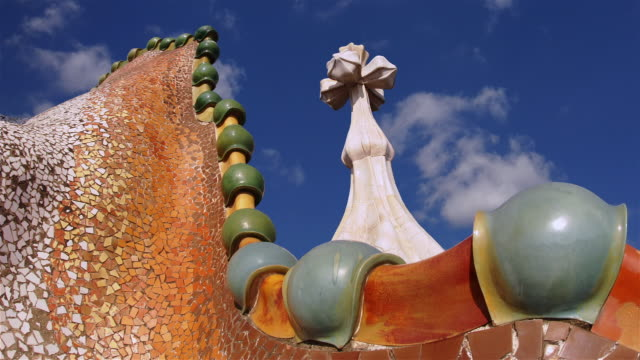 Detail of curved roof and turret on Casa Batllo with clouds passing overhead in fast motion / Barcelona, Spain