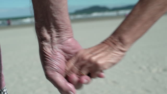 vídeos y material grabado en eventos de stock de detail of elderly couple hands on the beach - propuesta