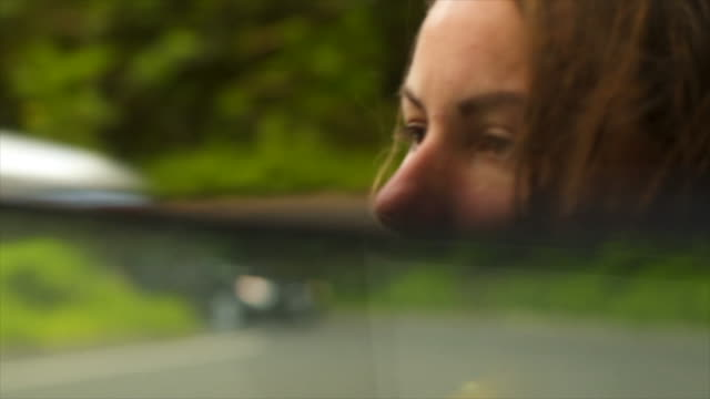 Detail of female driver looking in rear view mirror