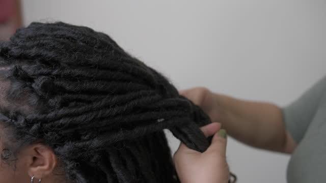 vídeos de stock e filmes b-roll de detail of female hands fixing hair dreadlocks - cabelo natural