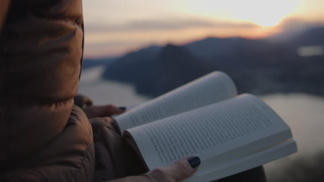 detail of female hands holding book at sunset at viewpoint - mid adult women stock videos & royalty-free footage