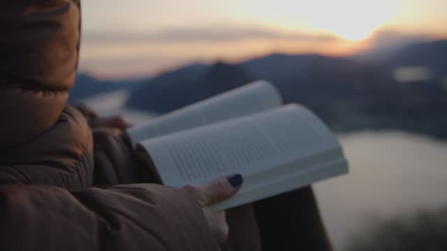 detail of female hands holding book at sunset at viewpoint - getting away from it all stock videos & royalty-free footage