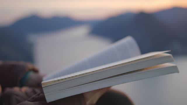 vidéos et rushes de détail de livre de fixation de mains femelles au coucher du soleil au point de vue - manteau et blouson d'hiver