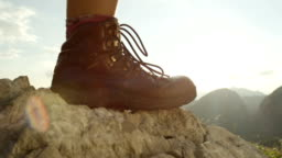 CLOSE UP: Detail of female hiking boots and hiking downhill on rough terrain
