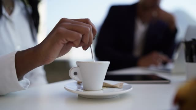 detail of female indian hand stirring espresso out business meeting - stirring stock videos & royalty-free footage