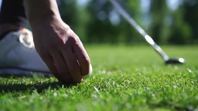 vidéos et rushes de détail du tee de golf sur le terrain herbeux - tee de golf