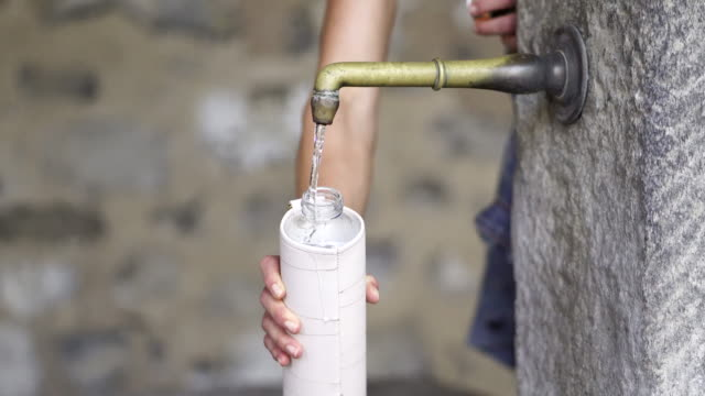 detail of hand filling up water bottle from old stone water fountain - filling stock videos & royalty-free footage