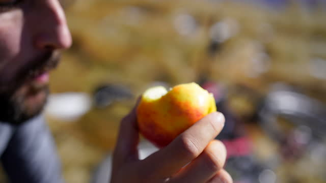 detail of hand holding apple, mans takes bite - one mid adult man only stock videos & royalty-free footage