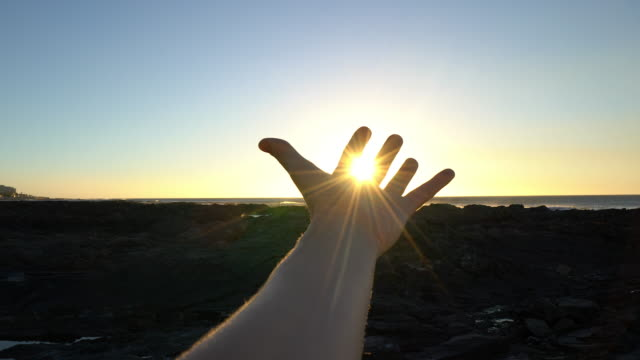 detail of hand stretched to cup rays of sunset - reaching stock videos & royalty-free footage