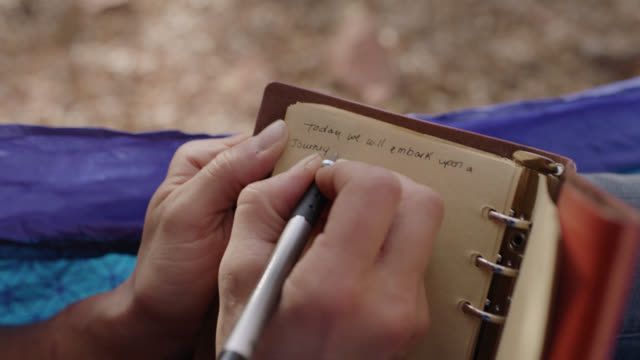 "ecu. detail of hand writing in journal from hammock in forest canopy. ""today we will embark upon a journey"" - blocco per appunti video stock e b–roll"