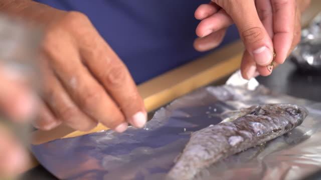 ベーキングのための魚を準備する手の詳細 - アルミホイル点の映像素材/bロール