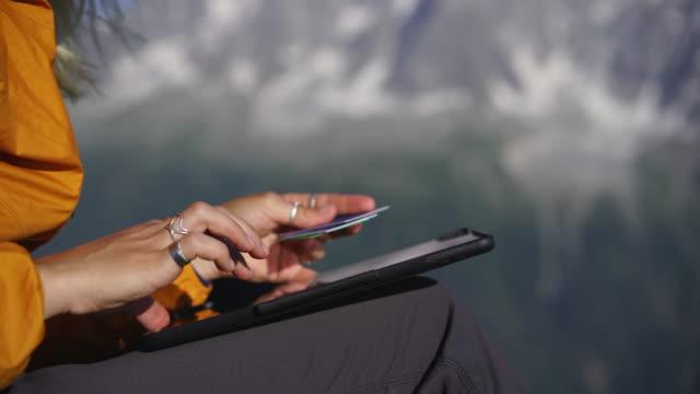 detail der hände mit kreditkarten, die online-zahlung auf tablet im freien auf berggipfel - making money stock-videos und b-roll-filmmaterial