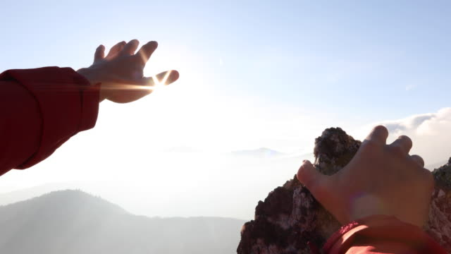 detail of hiker's hand reaching over mountains at sunrise - reaching stock videos and b-roll footage