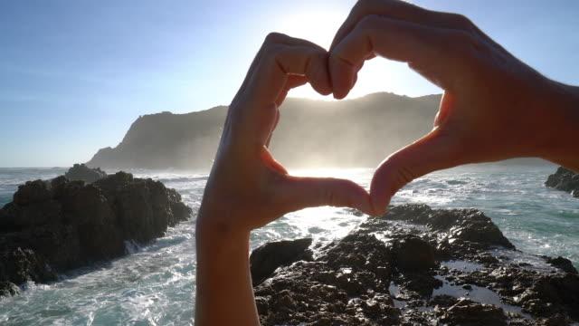 Detail of human's hand making heart shape frame on seascape