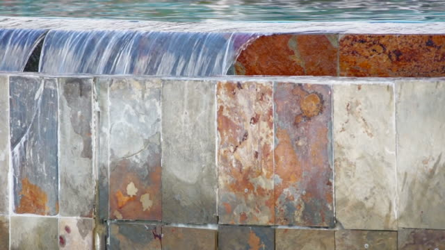 Detail of infinity edge pool, water falling into slate wall