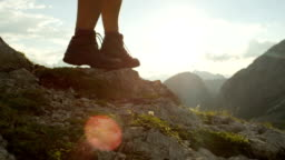 CLOSE UP: Detail of leather boots and hiker walking on dangerous mountain ledge