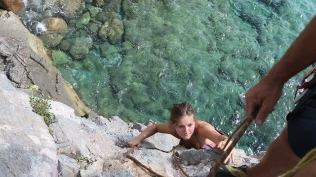 detail of man belaying young woman on rock climb above sea - belaying stock videos & royalty-free footage