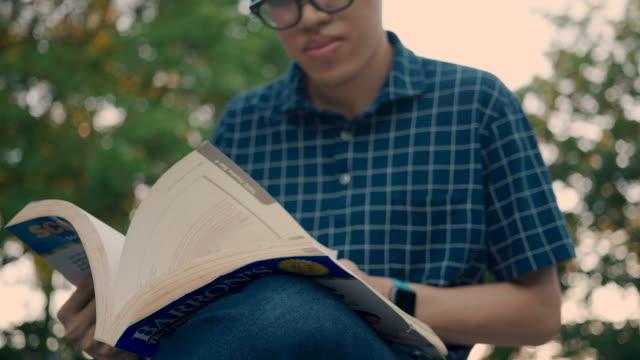 vidéos et rushes de détail des mains d'hommes retenant le livre - littérature