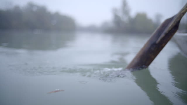 detail of old style wooden paddle entering water - oar stock videos & royalty-free footage