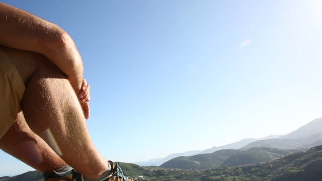 Detail of person relaxing on rock ledge, above valley, mountains