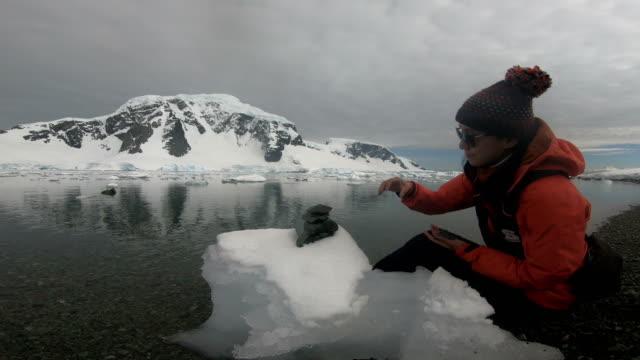 vidéos et rushes de détail de la personne, empilement de roches de l'antarctique - manteau et blouson d'hiver