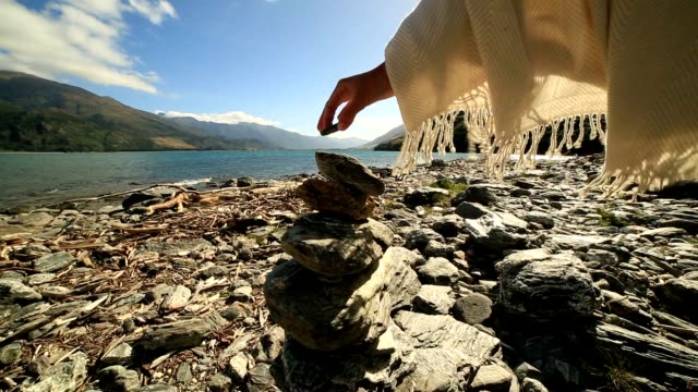 detail of person stacking rocks by the lake at sunrise - stack rock stock videos and b-roll footage