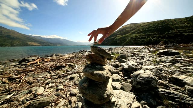 Detail of person stacking rocks by the lake at sunrise