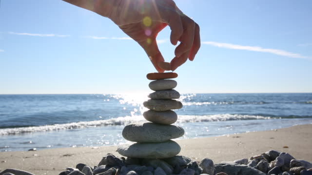 detail of person stacking rocks on beach, sunlit water - vertrauen stock-videos und b-roll-filmmaterial