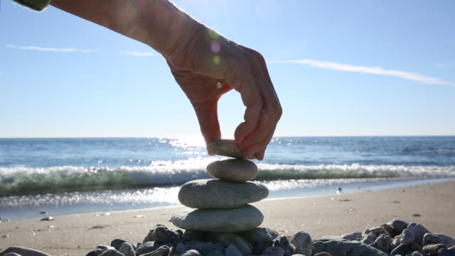 Detail of person stacking rocks on beach, sunlit water
