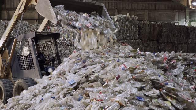 vídeos de stock, filmes e b-roll de detalhe da reciclagem de garrafas pet na reciclagem de fábrica de plástico com uma colher de veículo - grupo grande de objetos