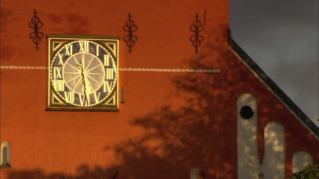cu detail of red building with gilded clock on wall / vaxjo, sweden - vaxjo stock videos & royalty-free footage