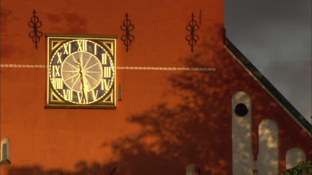 cu detail of red building with gilded clock on wall / vaxjo, sweden - romersk siffra bildbanksvideor och videomaterial från bakom kulisserna