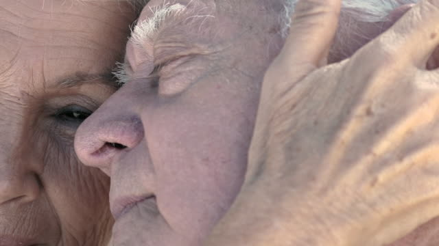 cu detail of senior woman face with camera moving to her hand making affection on husband. - serene people stock-videos und b-roll-filmmaterial