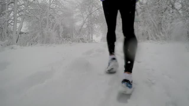 Detail of shoes running through fluffy snow