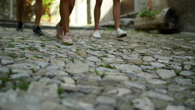 detail of shoes walking on cobblestones in old town - human limb stock videos & royalty-free footage