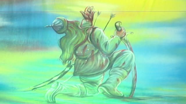 vídeos y material grabado en eventos de stock de detail of traditional imagery shown during the ashura commemorations. the painting depicts a man felled by arrows during the battle of karbala. - ashura