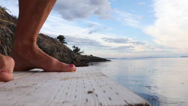 Detail of woman's legs, walking on pier above tidal lagoon, sunrise