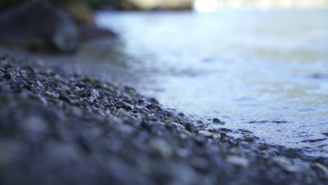 vídeos de stock, filmes e b-roll de tiro detalhado de uma costa do lago batendo em pequenas rochas - pedra solta