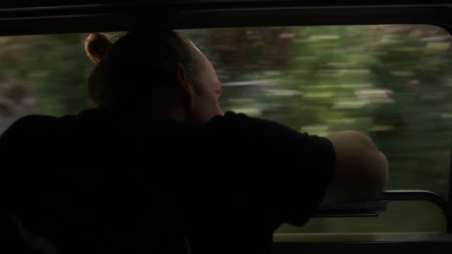 detail shot of a man looking out of a moving train window - stare in piedi video stock e b–roll