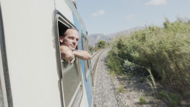 detail shot of a man looking out of a moving train window - leaning stock videos & royalty-free footage