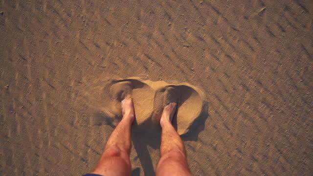 vídeos de stock e filmes b-roll de detail shot of a man wiggling bare feet into the sand - descalço