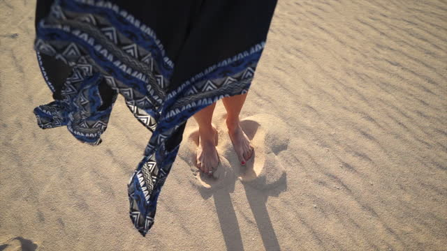 裸足で砂の中に立っている黒いドレスを着た女性の詳細ショット - トーリング点の映像素材/bロール