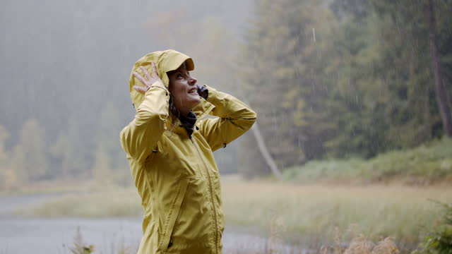detailaufnahme einer frau im wald, die einen regnerischen tag mit genuss erlebt - standing stock-videos und b-roll-filmmaterial